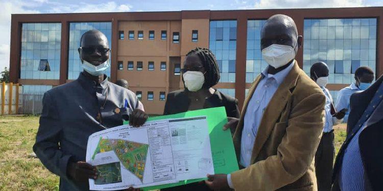 Muni University Secretary Rev. Fr. Pacutho, (UCI) Board representative Ms Gertrude Nakigudde and UCI Executive Director Dr. Jackson Orem displaying the land offer.